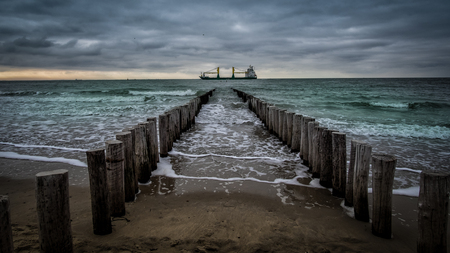 Big ship crossing the wooden pier during cloudy weather at the beach in Vlissingen, Zeeland, Netherlands