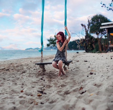 Young woman with red hair is relaxing on the beachside Stock Photo