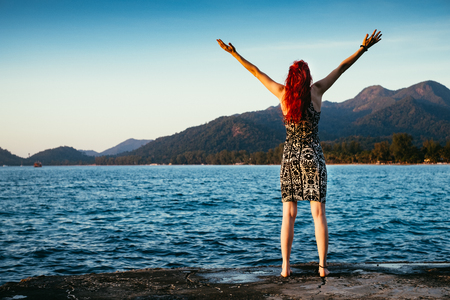 Girl with red hair is appreciating the wonderful view near the ocean with mountains and forest