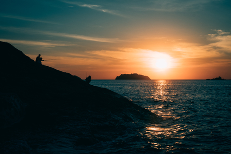 Silhouette of rocky cliff with fishermen during sunset on tropical island in the evening