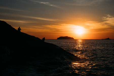 Silhouette of rocky cliff during sunset on tropical island at Ko Chang, Trat, Thailand Stock Photo