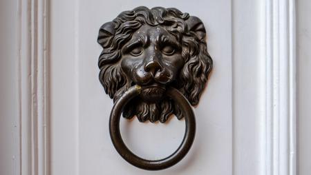 Ancient dark Doorknob in the shape of a Lion at white door