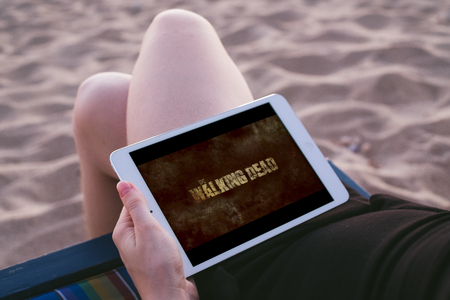 Koh Lanta, THAILAND - MARCH 18, 2018: Young woman at the beach with iPad in her hand showing WALKING DEAD INTRO Editorial