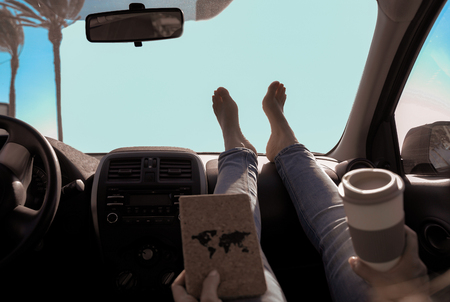 Woman drinking cappuccino inside car with feet on dashboard - Girl relaxing in car trip reading book with palms and clear sky in the background - Traveler concept - Focus on feet - Image Standard-Bild - 123888860