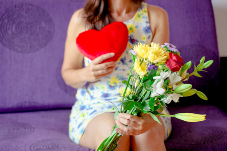 Bouquet of flowers and red heart in the hands of a woman - Image Standard-Bild - 123888865