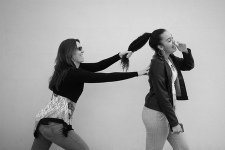 Having fun / Mother pulling her daughter's hair family problem concept. Black and white. - Image Standard-Bild - 123888871