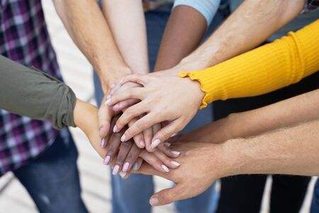 Young people putting their hands together. Friends with stack of hands showing unity and teamwork - Image Standard-Bild - 134767184