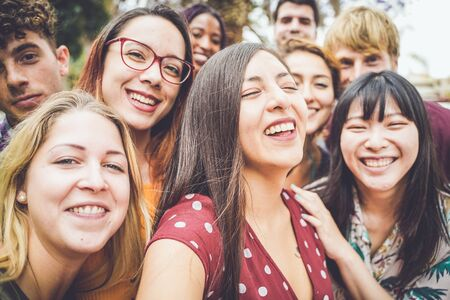 Friendship, leisure and summer concept - group of happy smiling friends outdoors. tourism, travel, people, leisure and technology concept. - image Standard-Bild - 134767473