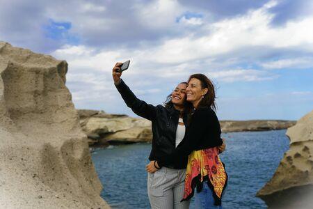 Having fun european mum and latin daughter in a day off. Enjoying a selfie mum and daughter in a wonderful Paradise coast - Focus on face - Image Standard-Bild - 131918737