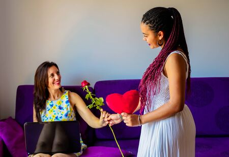 Happy mother's day! Latin daughter congratulates mom and gives her red rose and a red heart. Mum and girl smiling. mum working with laptop Family holiday and love time. -Image Standard-Bild - 131918409