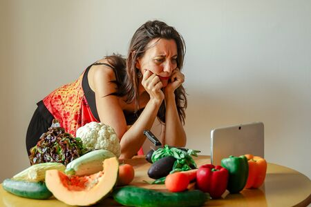 Woman using a tablet computer to cook in her kitchen. Woman looking a fruits recipe. Kitchen woman making healthy food with tablet computer. Focus on the face- Image Standard-Bild - 131917571