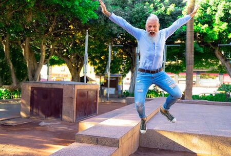 Smiling senior man relaxing in the park. Mature male having fun and jumps like a child. - Focus on this face - Imagen Stock Photo