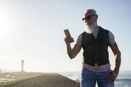 Trendy senior man using smartphone app near of the sea - Mature fashion male having fun with new trends technology - Tech and joyful elderly lifestyle concept - Focus smartphone - Image Standard-Bild - 132011547
