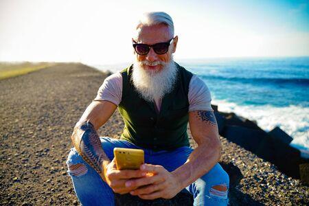 Trendy senior man using smartphone app near the sea - Mature fashion male having fun with new trends technology - Tech and joyful elderly lifestyle concept - Focus on his face - Image Standard-Bild - 131918625