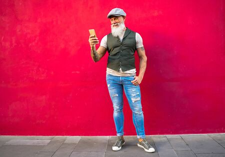 Smiling senior man relaxing in the city. Mature male having fun with new technology trends. - Focus on this face - red wall - Imagen
