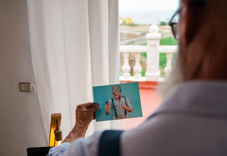 Elderly man holding photo of the carnival day. Hand holding picture of amused gentleman. Happy memories concept. Image Standard-Bild - 134768676