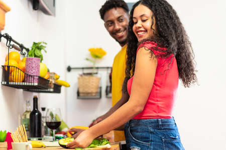 Happy young couple cooking in kitchen. Beautiful young couple smiling while cooking healthy food in kitchen at home. Man looking his girlfriend. Love and food concept.