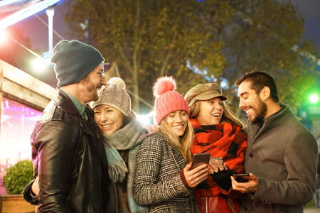 Happy Group of friends walking in London street. Young people hanging out ready for christmas night. Millennial people smiling for a joke. Christmas and friendship concept.Focus on girl with pink hat