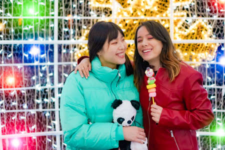 Young teenagers having fun together in christmas date. Happy young friends with a teddy bear and sweet candy in their hands. Travel, love and friendship concept.