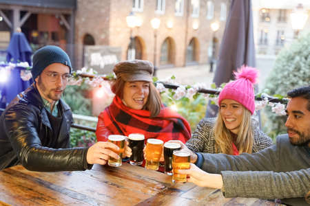 Group of millennial friends drinking and toasting beer at the bar in new year date. Friendship and travel concept. People sharing a beer together at cool vintage pub on Christmas date. Focus on beer.