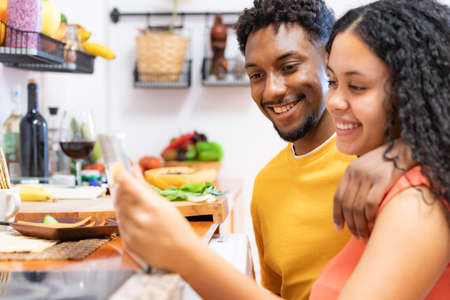 Happy young couple looking the recipe on the tablet. Beautiful young couple smiling preparing healthy food in kitchen at home. Technology, love and food concept.