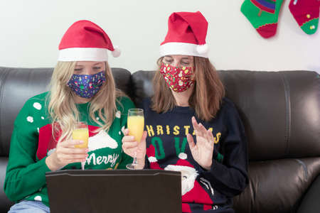 Young women with masks for viruses and wearing Christmas hats drinking cocktails talking to friends on virtual video call celebrate Christmas or happy new year in distance online conference chat on computer at home.