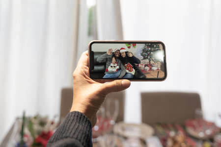 Video call with family on online in christmas time, hand holding the smartphone, father looking the sons on lockdown. Family and technology concept. Standard-Bild