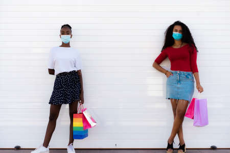 Spring shopping during quarantine conception: fashionable women wearing protective mask posing with colorful paper bags. White background. Copy, empty space for text