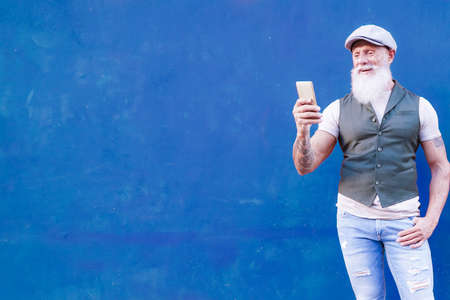Portrait of elderly man looking a video on the cellular phone. Man isolated on blue wall background. pensioner and technology concept.
