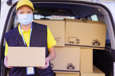 Portrait of delivery woman wearing face protective mask for virus spread prevention.