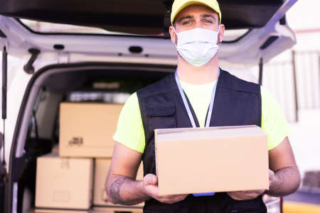 Delivery man employee in yellow cap and t-shirt uniform face mask hold empty cardboard box. virus  and buy concept.
