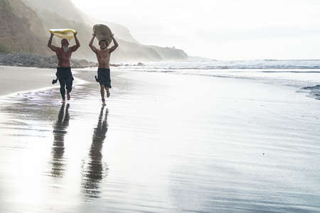 Father and son doing surfing in a perfect day. Friends going out into the ocean. Sporty people lifestyle and extreme sport concept.