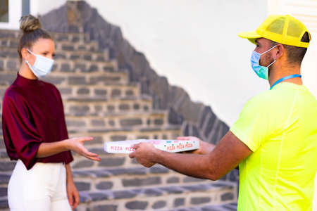Delivery man employee in yellow cap and t-shirt uniform face mask hold food order pizza box. Service quarantine pandemic  virus flu   concept.