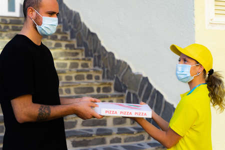 Delivery woman employee in yellow cap and t-shirt uniform face protective mask hold food order pizza box. Standard-Bild