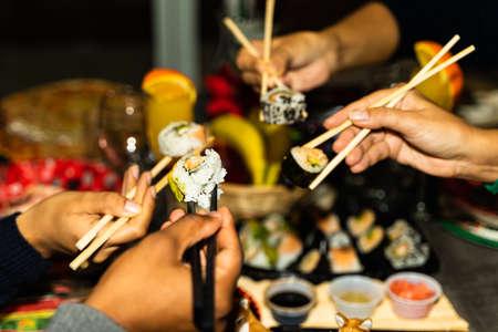 People hands hold sushi rolls with sticks. Couples eating and sharing sushi roll, maki, nigiri, uramaki. Food concept. Standard-Bild