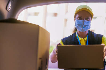 Delivery woman services courier during the Coronavirus (COVID-19) pandemic, courier wearing medical mask for safety protection from virus infection working with cardboard boxes. Standard-Bild