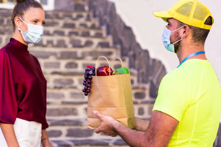 Delivery caucasian man grocery delivery courier man in yellow uniform and face mask with little box with fresh fruit and vegetable. Food and delivery concept.