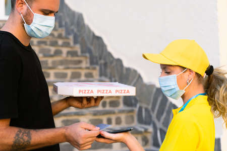 Delivery woman employee in yellow cap and t-shirt uniform face protective mask. Man hold a pizza box and pay with credit card. Coronavirus and buy concept.