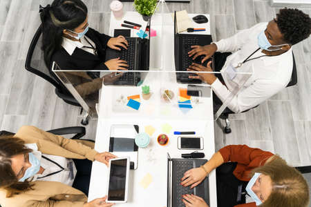 Top view of multi ethnic creative people in office. Group of business people are working together with laptop, tablet, smartphone, notebook. Perfect team in coworking. Technology and job concept. Standard-Bild