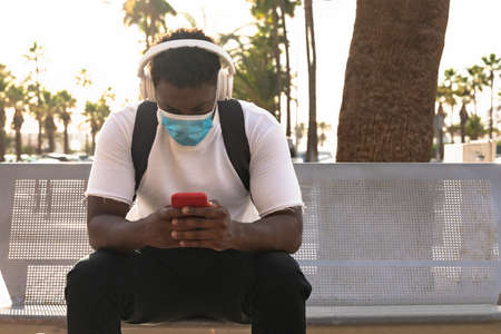 Man listening to the music and looking videos, Boy waiting girlfriend, Millennial person with a protective mask for coronavirus.