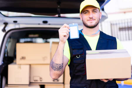 Professional delivery man. Young courier holding a cardboard box and showing card. Job and buy concept.