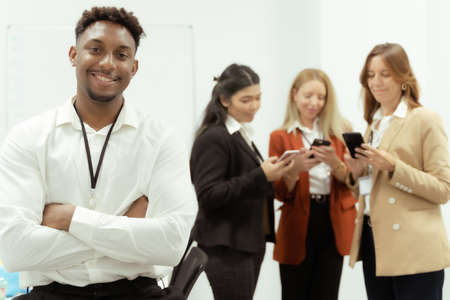 Young African male employee in formal clothes standing in the office. Group of people working behind with smartphones. Job concept.