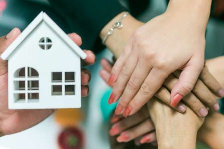 Young people putting their hands together. Friends with stack of hands showing unity and teamwork. Top view of hands and little white house. Real estate agent concept. Focus on hands.