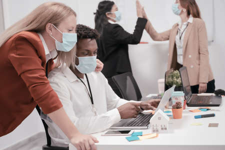 Multiracial creative people in office. Four people in office with protective masks without distance for coronavirus. Technology, covid 19 and job concept.