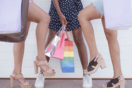 Closeup of legs of women standing on the floor. Women with different shoes and shopping bags. Friendship and buy concept. Standard-Bild