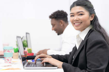 Attractive asian young confident businesswoman sitting at the office table with of colleague in the background, working on laptop computer. Job and technology concept. Standard-Bild