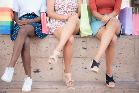Three girls sitting on stairs and chatting after buying presents. Happy women are sitting relaxed on steps of the shopping center. Shop and friendships concept. Standard-Bild