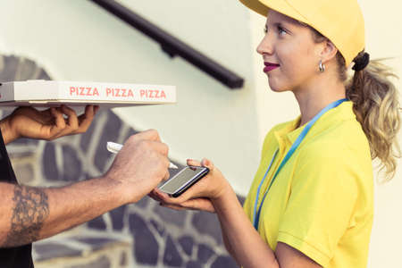 Messenger woman with a smartphone for payment. Man holding a pizza box and put the signature for carrier with payment terminal. Package delivery concept.