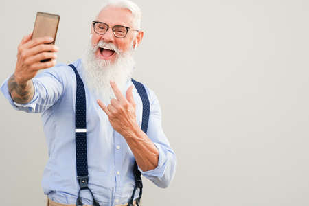 Portrait of attractive hipster man. Positive gray-haired pensioner making selfie. Technology and elderly concept.