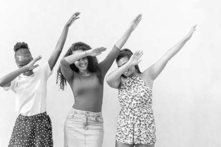 Three nice-looking good-dressed cute sweet gorgeous brunette hair lady stand isolated on white wall make dabbing movement. Black and white picture.